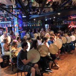 A group of people learning how to play the Bodhrán at a Creative Events Bodhrán Session