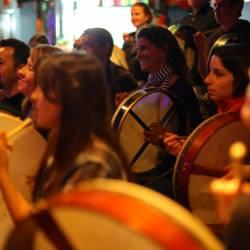People playing a rhythm on the Bodhrán at a Creative Events Bodhrán Session