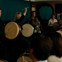An Irish musician showing a group how to hold the cipin at a Creative Events Bodhrán Session