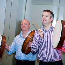 People beating on a Bodhran at a Creative Events Drum 4 Fun event