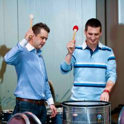 Two men learning the rhythm on large base drums at a Creative Events Drum 4 Fun event