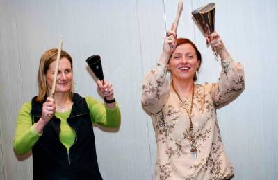Two women learning to play the Agogo bells at a Creative Events Drum 4 Fun event