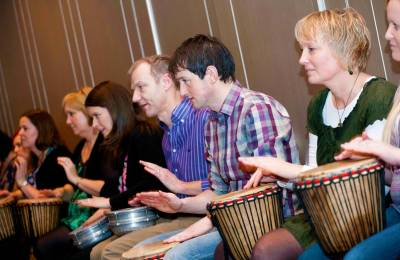 A group learning a rhythm on different drums at a Creative Events Drum 4 Fun event