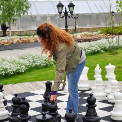 Large scale chess board being played by a woman who is picking up one of the chess pieces at a City Challenge event organised by Creative Events