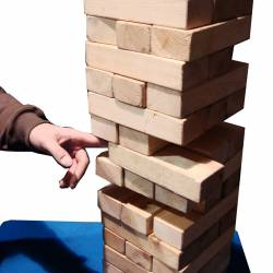Large scale jenga game being played on a top of a blue table at a City Challenge event organised by Creative Events