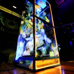 Grab a grand box lit up with lights while money is being blown around the see through box at a Company Challenge event organised by Creative Events
