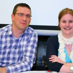 Two team members smiling as they take part in the Quiz Show organised by Creative Events