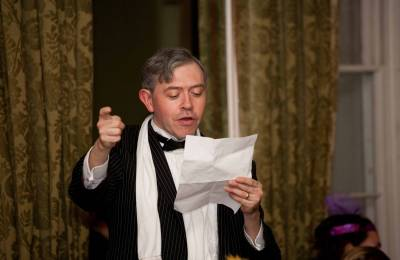 Actor in Character reading from a page at a Creative Events Murder Mystery
