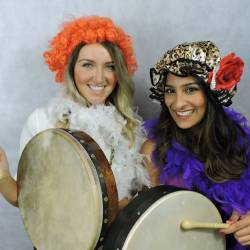 Two women wearing Irish wigs and holding bodhrans at a Creative Events Trad Irish Experience