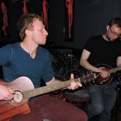 Two Irish musicians playing guitar and banjo at a Creative Events Trad Irish Experience