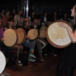 A group learning to play the bodhran at a Creative Events Trad Irish Experience