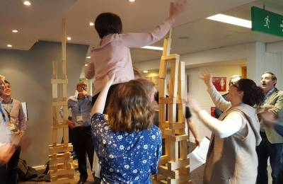 A group building a tall structure using giant jenga pieces at a Creative Events corporate team building event