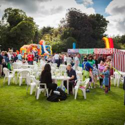 People sitting at tables with carnival stalls in the background at a Creative Events Company Carnival