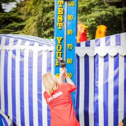 A woman playing test your strength at a Creative Events Company Carnival