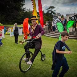 A performer on an old bicylce at a Creative Events Company Carnival