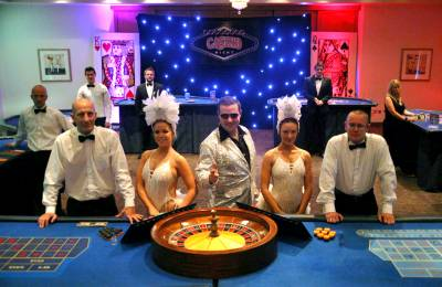 Performers and croupiers posing at a roulette table at a Creative Events Casino Party