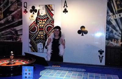 A woman posing at giant playing cards at a Creative Events Casino party
