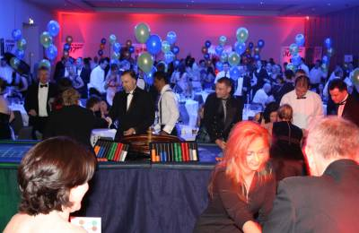 Groups of people playing at different Poker Tables at a themed event run by Creative Events