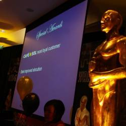 A screen with a large oscar statue at a Creative Events Oscars Night