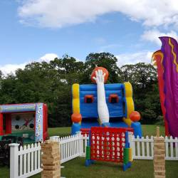 Inflatables set up behind a giant games area at a Creative Events Family Fun Day