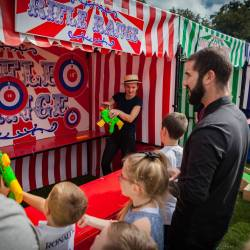 A family playing a carnival stall game at a Creative Events Family Fun Day