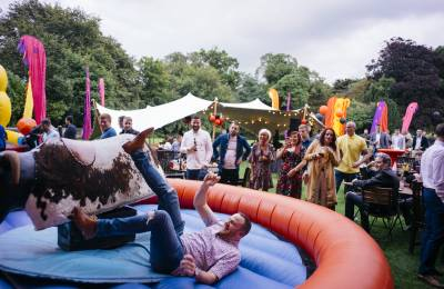 A man falling of a buckin bronco and landing on the bouncing castle