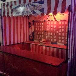 Carnival stall set up with playing cards at the back where people can through darts and win prizes at a Company Olympics event organised by Creative Events