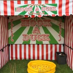 """Carnival stall set up with a green and white sign saying """"Hook A Duck"""" with a yellow mini pool with ducks in it , at a Company Olympic event organised by Creative Events"""