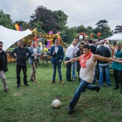 A group of people gathered around as their colleague kicks a ball