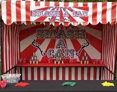 Carnival stall set up with tiered cans at the back of the stall where people can knock them over