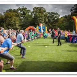Two teams playing against each other in a game of tug of war at a Company Olympics event organised by Creative Events