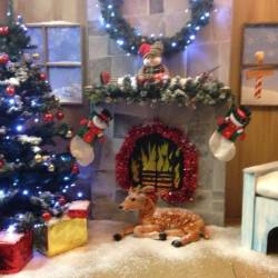 A reindeer sitting under a fire place in a Creative Events Santa's Grotto