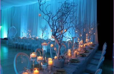 White tables with candles and tree decorations at a Creative Events Winter Wonderland event