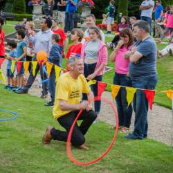 A man participating in a hula hoop race at a Creative Events Summer Family Fun Day