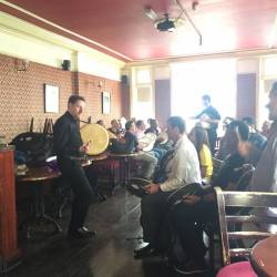 A musician showing a group how to hold the Irish Bodhran at a Creative Events City Challenge