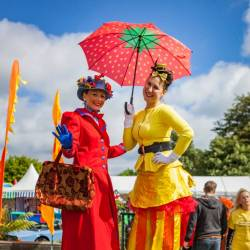Two stilt walker performers posing in the sunshine at a Creative Events Summer Family Fun Day
