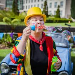 A children's performer blowing bubbles at a Creative Events Summer Family Fun Day