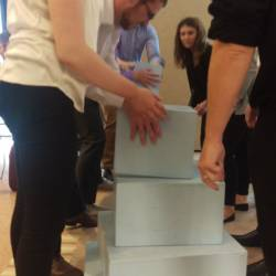 A team figuring out the Tower of Hanoi challenge at a Creative Events Company Challenge