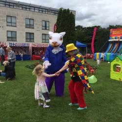 Two characters mingle with a child at a Creative Events Summer Party