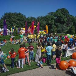 People gather to watch relay races at a Creative Events Summer Family Fun Day