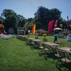A wide shot of the setup with tables, flags and inflatables at a Creative Events Summer Family Fun Day