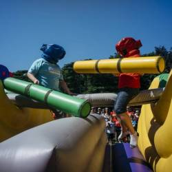 People on an inflatable gladiator jousting at a Creative Events Summer Family Fun Day