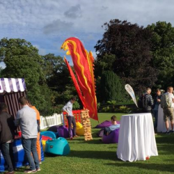 People playing on carnival stalls and relaxing in the chill out zone at a Creative Events Summer Party