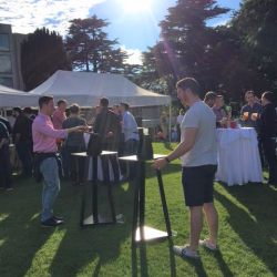 People playing a wooden sling shot game at a Creative Events Summer Party
