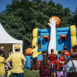 A group of people gather to watch a competition on an inflatable basket ball shoot out at a Creative Events Summer Family Fun Day