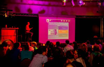 Teams looking at a screen for the next question at a Creative Events Digi Quiz