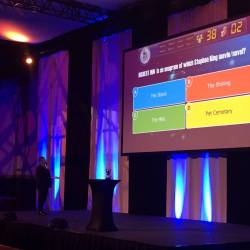 A screen on stage at a Creative Events Digi Quiz