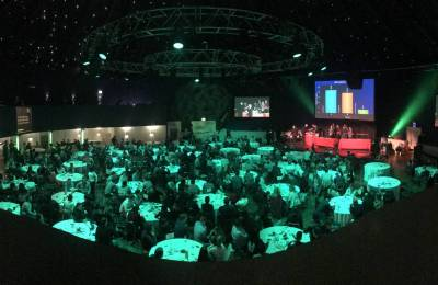 Teams sat at tables facing stage at Creative Events Cube Gameshow