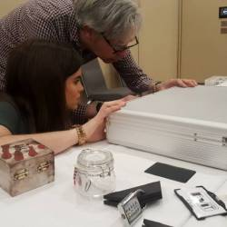 A team working on a briefcase lock at a Creative Events Table Top Escape Corporate Team Building event