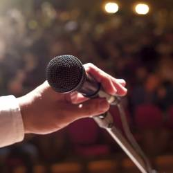 A person holding a microphone in front of a crowd at a Creative Events Instant Choir